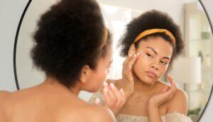 femme qui regarde la peau de son visage dans le miroir