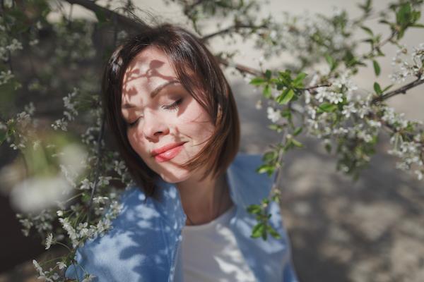 Femme qui sourit de profil au milieu de fleurs blanches du printemps.