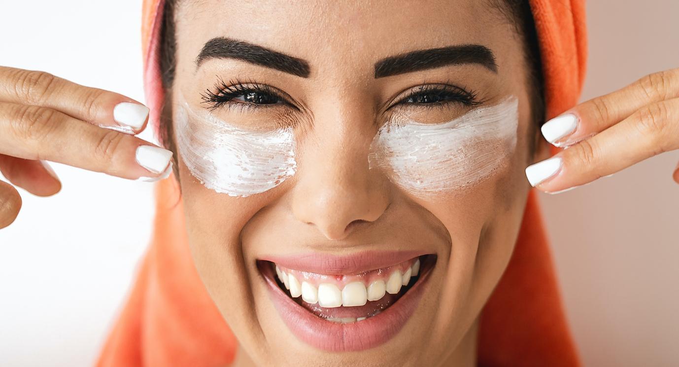 femme avec une serviette sur la tête et un masque dans le visage qui sourit.