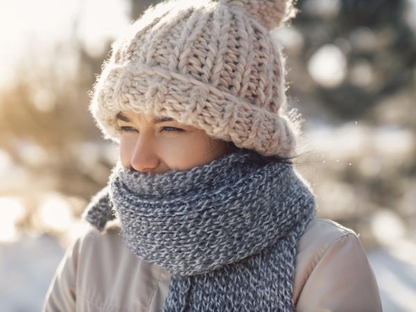 femme à l'extérieur à l'hiver qui porte une tuque, un manteau et un foulard