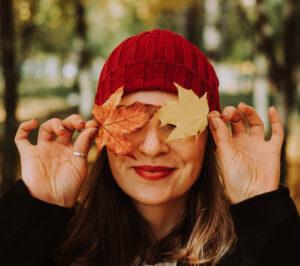 Femme portant une tuque rouge qui se cache les yeux avec des feuilles d'automne
