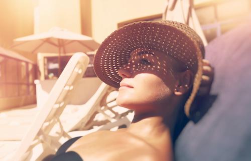 Femme qui bronze au soleil avec de la lotion solaire
