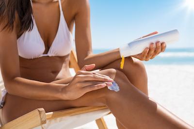 Femme qui applique de la crème solaire