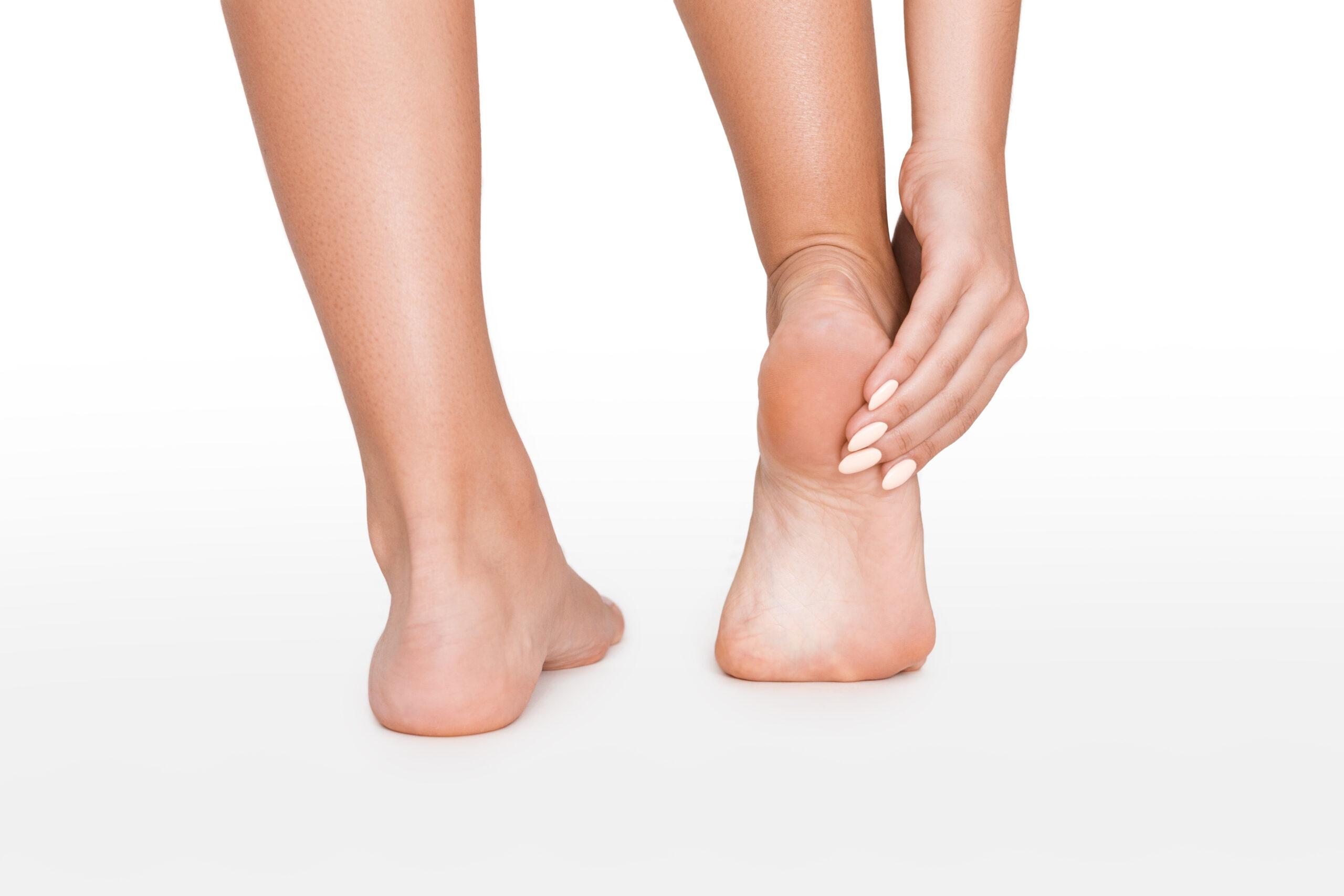 pieds de femme avec celui de droite levé et talon dans les mains