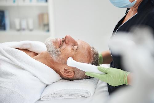 Homme au salon se faisant faire un traitement de photorajeunissement au visage