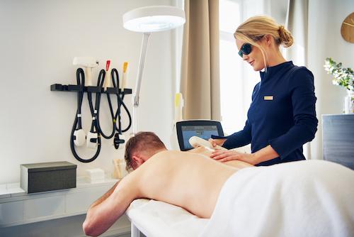 Homme se faisant epiler le dos au laser par une femme estheticienne