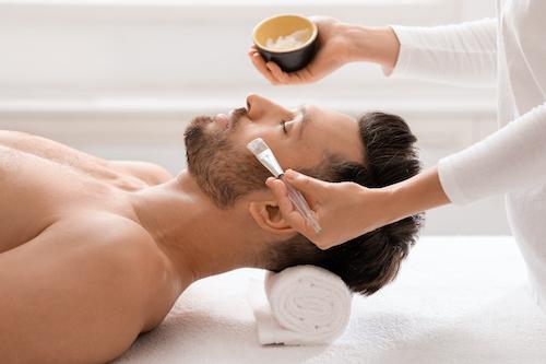 Homme au salon se faisant faire un traitement du soin du visage